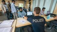 Ein Beamter der Bundespolizei überprüft im Juli 2015 im Notquartier der Bundespolizeiinspektion in Passau die Identität von Flüchtlingen.