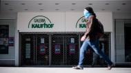 Ein Mann geht mit Maske am Eingang der geschlossenen Filiale der Kaufhauskette Kaufhof in Essen vorbei.