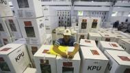 Für die Präsidentschaftswahlen in Indonesien bereitet ein Arbeiter Wahlurnen und Stimmzettel vor.