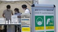 Mitarbeiter der Olympischen Spiele nehmen PCR-Tests der Athleten ab.