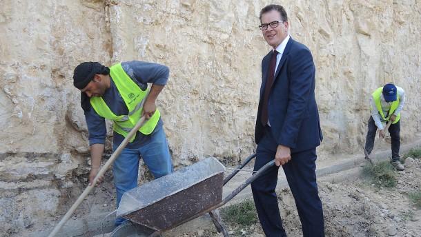 © dpa Kooperation ist keine Einbahnstraße: Bundesentwicklungsminister Gerd Müller (CSU) packt Ende 2016 bei einem Bauvorhaben der deutschen Entwicklungsbank KfW in Jordanien mit an – zumindest für ein Foto.