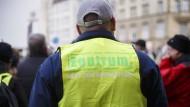 """Ein Kundgebungsteilnehmer trägt eine Weste der Gruppierung """"Zentrum Automobil""""."""