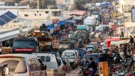 Ein türkischer Militärkonvoi inmitten von Fahrzeugen flüchtender Zivilisten im Norden der Provinz Idlib.