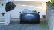 Ein E-Auto von Tesla lädt vor einer Garage in Norwegen auf.