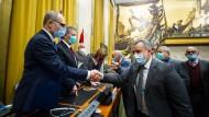 Vertreter der beiden Parteien, die sich in Libyen bislang gegenseitig bekämpften, geben sich am 23. Oktober in Genf die Hand.