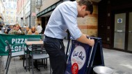 """Ein Kellner vor einem Aufsteller mit der Botschaft """"Auswärts essen um zu helfen"""" Anfang August in London"""