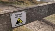 """Warnschild """"Danger Cliff Edge"""" an den White Cliffs von Dover, England. Im Hintergrund ist der Hafen zu sehen."""