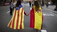 Friedfertige Vertreter zweier Nationalismen: Demonstrantinnen in Barcelona, eingehüllt in die katalanische (links) und die spanischen Flagge.