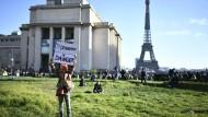 """Paris am 21. November: Auf dem Place du Trocadéro hebt eine Demonstrantin ein Schild mit der Aufschrift """"Democracy in danger"""" in die Höhe."""