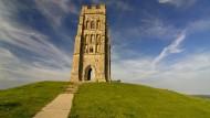 Von Avalon, heißt es in der Sage, wird Artus eines Tages wiederkehren: Manche halten die mythische Insel für den Glastonbury Tor, auf dessen Kuppe die Ruine des Turms von St. Michael's steht.