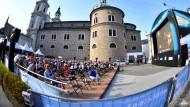"""Besucher sitzen während der Freiluft-Übertragung der Festspiel-Premiere von """"Elektra"""" von Richard Strauss in der Felsenreitschule auf dem Kapitelplatz in Salzburg."""