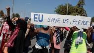 """Migrantinnen und Migranten aus dem zerstörten Camp Moria halten bei einem Protest auf der Insel Lesbos ein Schild mit der Aufschrift """"EU, save us, please"""" (EU, rette uns bitte)."""