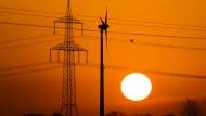 Niedersachsen, Sehnde: Ein Vogel fliegt bei Sehnde in der Region Hannover neben einer Hochspannungsleitung und einem Windrad vor der aufgehenden Sonne.