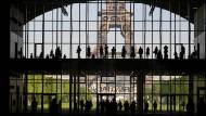 """Besucher versammeln sich während einer Präsentationsbesichtigung des """"Grand Palais Ephemere"""", während im Hintergrund der Eiffelturm zu sehen ist."""