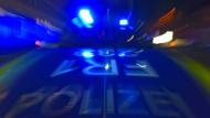 Ein Polizeifahrzeug steht in Deutschland mit Blaulicht auf der Straße. (Archivbild)