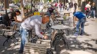 Angestellte eines Cafés auf der Düsseldorfer Kö streichen die seit der Corona-Krise ungenutzten Stühle.