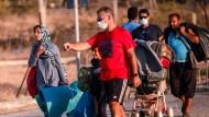 Migranten und Flüchtlinge ziehen in das neue, provisorisch aufgebaute Zeltcamp auf Lesbos nahe Panagiouda.
