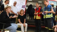 Bundeskanzlerin Angela Merkel (links, CDU) und Malu Dreyer (zweite von links, SPD), Ministerpräsidentin von Rheinland-Pfalz, sprechen am Sonntag in Schuld mit Helfern.