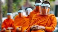 Buddhistische Mönche beten am Dienstag in Bangkok. Die Plastikvisiere sollen die Ausbreitung des Coronavirus verhindern.