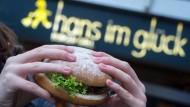 """Eine junge Frau hält einen vegetarischen Burger der Burger-Kette """"Hans im Glück"""" in der Hand. Die Kette bekommt einen neuen Eigentümer."""