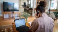 Eine Frau arbeitet in ihrem Wohnzimmer im Homeoffice und nimmt an einer Telefonkonferenz teil.