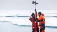Um die Folgen eines sich ändernden Eis- und Stofftransports für das Ökosystem Arktis besser abschätzen zu können, entnehmen zwei AWI-Forscher Eiskern-Proben.