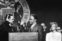 Judge Charles E. Freeman swears in Harold Washington as Chicago mayor on April 29, 1983. Outgoing mayor Jane Byrne is at right.