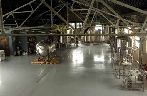 The brewery seen from the back stairs, with a 15-barrel brew house, three 15-barrel fermenters, one bright tank, and plenty of room for expansion. The fermenter on its side belongs to South Loop Brewing.