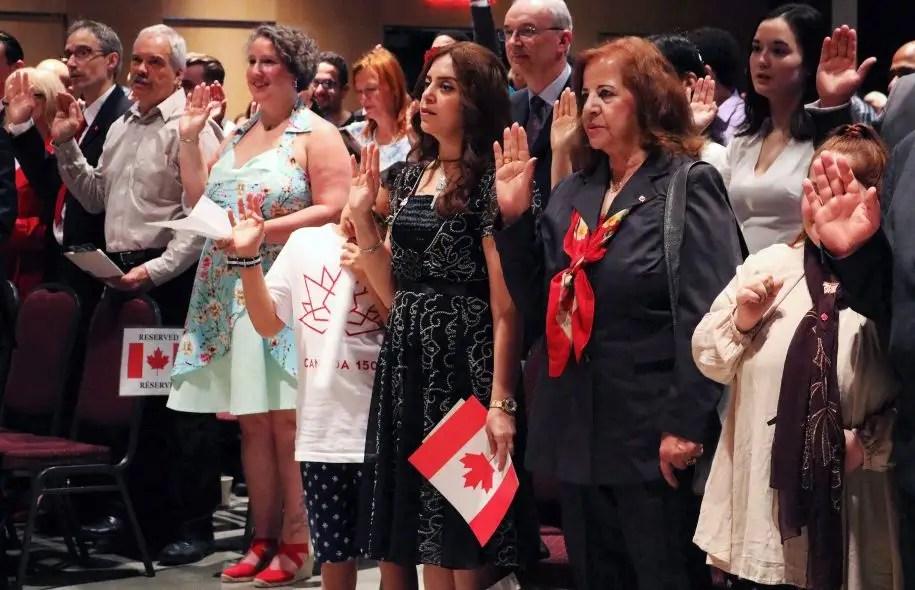Des immigrants ayant obtenu la citoyenneté canadienne au moment de prêter serment. Le gouvernement fédéral a fait connaître mercredi ses nouvelles cibles en matière d'immigration.