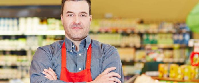 Store manager standing with his arms crossed in a supermarket