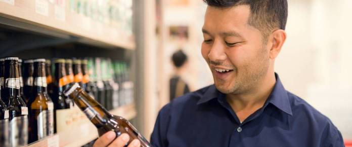 Handsome Young Asian man happy selecting a beer from supermarket.