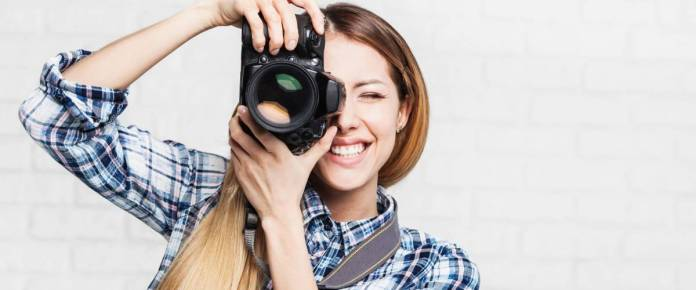 Woman photographer takes images with dslr camera