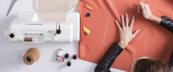 Top view of a girl making a pattern on a red piece of material. Fashion design conceptual.