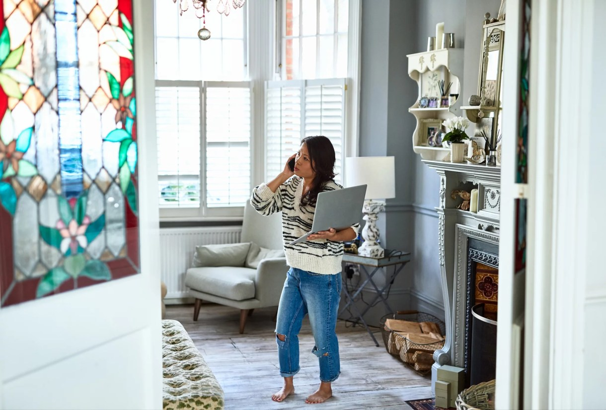 Mid adult woman in living room holding computer and using smartphone, listening to customer service advisor, on hold, patience, service