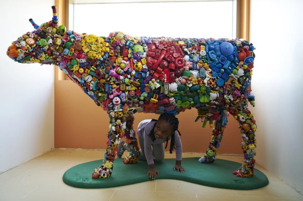 A child plays with one of the hospital's many art installations, a cow made from hundreds of donated children's toys.