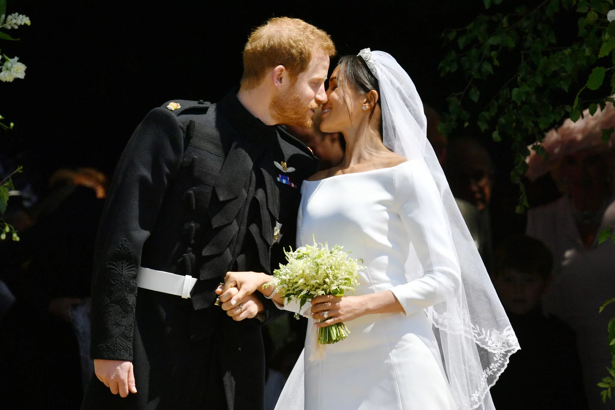Britain's Prince Harry, Duke of Sussex kisses his wife Meghan, Duchess of Sussex as they leave from the West Door of St George's Chapel, Windsor Castle, in Windsor, on May 19, 2018 after their wedding ceremony. (Photo by Ben Birchall / POOL / AFP)        (Photo credit should read BEN BIRCHALL/AFP/Getty Images)