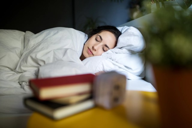 Young woman sleeping peacefully on her bed at home