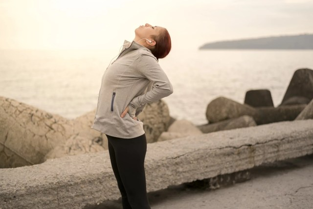 Photo taken on sunset in Bulgaria, Eastern Europe. Sporty young woman having back pains during workout.