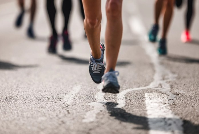 Unrecognizable marathon runner having a race on the road.
