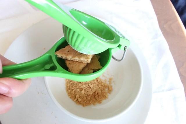 Dengan menggunakan pemeras jeruk, dapat meremukkan biskuit cracker