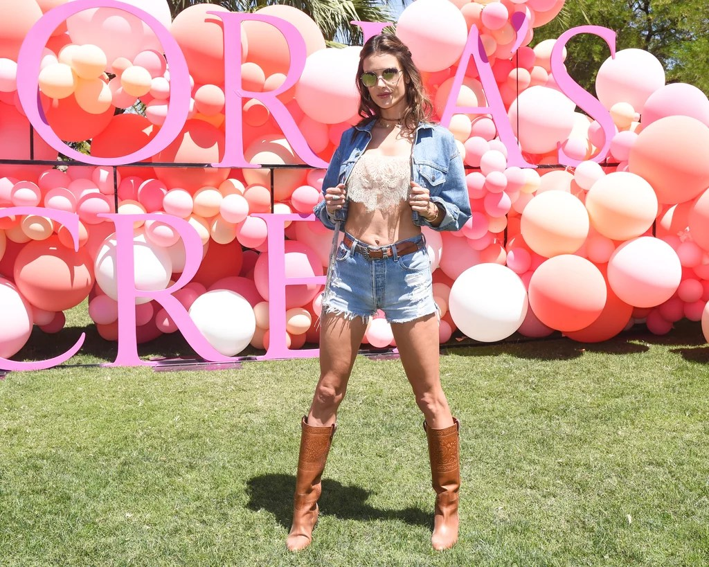 Alessandra Ambrosio wearing a crop top, knee-high boots, and denim shorts at the Victoria's Secret Angel Oasis.
