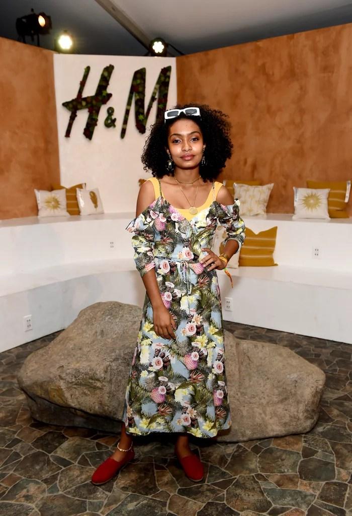 Yara Shahidi wearing a floral dress and flats at the H&M Loves Coachella tent.