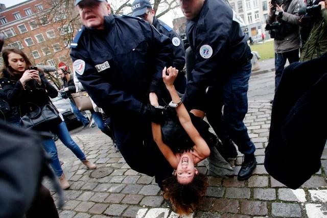 Petugas kepolisian menangkap aktivis Femen yang berusaha menghadang mobil yang ditumpangi Dominique Strauss-Kahn