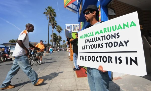 A man holds a placard advertising medica