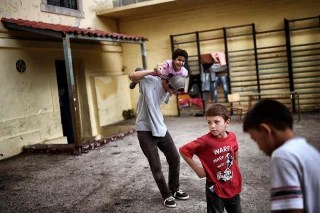Image: Children play at the yard of an abandoned school used by volunteers for hosting families of refugeees
