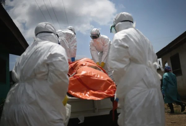 Image: An Ebola burial team loads the body of a woman, 54, onto a truck for cremation