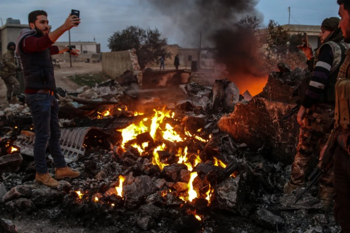 Image: People walk amidst the rubble of the Russian Sukhoi Su-25 fighter jet scattered on the ground, in Ma'saran village near Saraqeb city, in Eastern Idlib countryside, Syria, on Feb. 3, 2018.