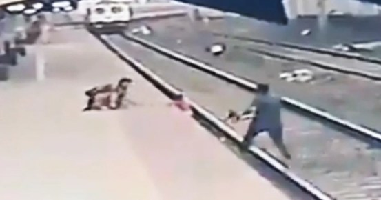 The video shows a man rescuing a child who fell on the train tracks as he approached the station