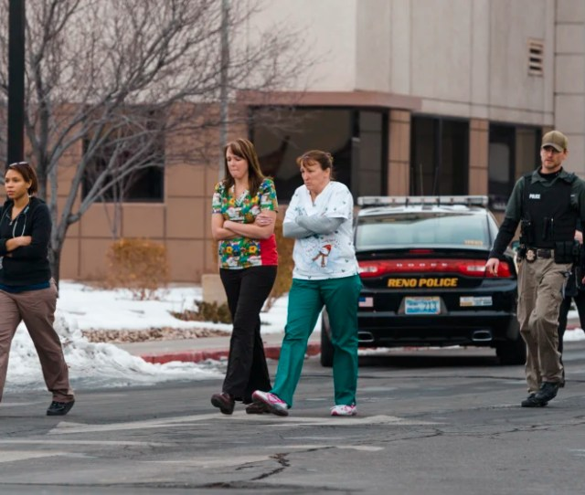 Officers Escort Witnesses To A Bus At The Renown Regional Medical Center After A Lone Gunman