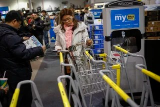 Shoppers look through discount pamphlets at the Best Buy electronics store in Westbury, N.Y. Retail experts say more shoppers are waiting for bigger discounts this year.